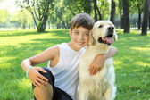 Tennager boy in the park with a dog — Stock Photo
