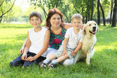 Mother and her two sons in the park with a dog — Stockfoto