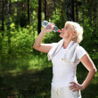 Elderly woman after exercising in the forest — Stock Photo #6205440