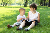 Children in the park reading a book — Stockfoto