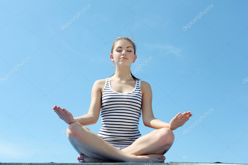 Portrait of a young woman doing exercises against blue sky  Stock Photo #6205349