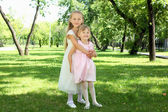 Two little sisters in the summer park — Foto Stock