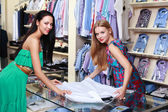 Girl seller helps shoppers — Stock Photo