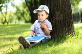 Portrait of a boy with a book in the park — Stock fotografie