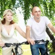 Young couple on the bikes in the park — Stockfoto