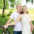 Young couple on the bikes in the park — ストック写真