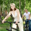 Young couple on the bikes in the park - Foto Stock