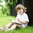 Portrait of little girl reading a book in the park — Stock Photo #6258271