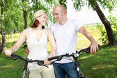 Young couple on the bikes in the park — Stock Photo