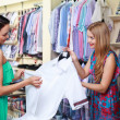 Girl seller helps shoppers - Stock Photo
