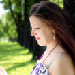 Portrait of young woman in the park - Stock Photo