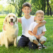 Two brothers in the park with a dog — Stock Photo