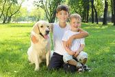 Dos hermanos en el parque con un perro — Foto de Stock