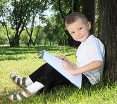 Parkta bir kitap ile bir çocuk portresi — Stok fotoğraf