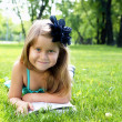 Portrait of little girl reading a book in the park - Stock Photo
