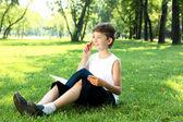 портрет мальчика с книгой в парке — Стоковое фото