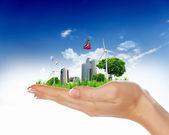 Ludzką ręką trzyma to miasto pełne zieleni — Zdjęcie stockowe