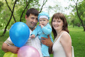 Young family together in the park — Stock Photo