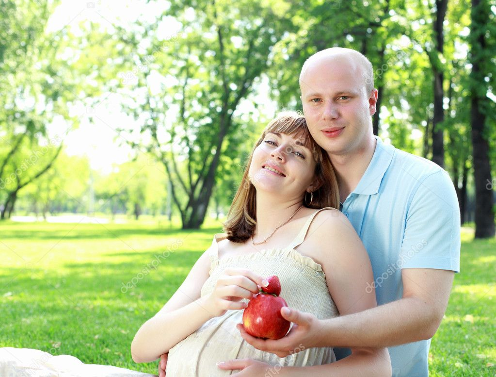 Young couple with a pregnant wife on picnic in the park — Stock Photo #6345191