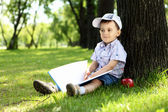 Portrait of a boy with a book in the park — Stockfoto