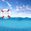 Rescue ring floating on blue waves - Stock Photo