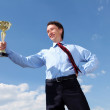 Stock Photo: Young businessman with a golden cup