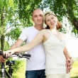 Stock Photo: Young couple on the bikes in the park