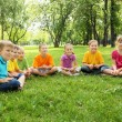 Group of children sitting together in the park - Foto Stock