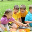 Group of children sitting together in the park — Stock Photo #6582825