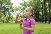 Little girl in the park blowing bubbles — Stock Photo