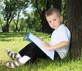 Portrait of a boy with a book in the park — Стоковое фото