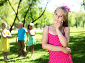 Little girl in summer park with friends — Stock Photo