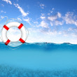 Rescue ring floating on blue waves — Stock Photo #6619612