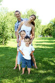 Family with two children in the summer park — Stok fotoğraf