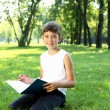 Stock Photo: Portrait of a boy with a book in the park