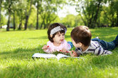 Children in the park reading a book — Photo