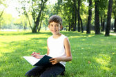 Portrait of a boy with a book in the park — Foto de Stock