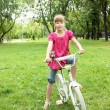 Girl with a bike in the park - Stock Photo