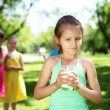 Stock Photo: Girl drinking milk in summer park