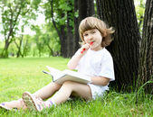 Portrait of little girl reading a book in the park — Stok fotoğraf