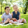 Children in the park reading a book — Stock Photo