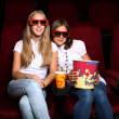 Royalty-Free Stock Photo: Two young girls watching in cinema