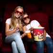 Two young girls watching in cinema — ストック写真