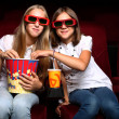 Two young girls watching in cinema — Stock Photo #6692670