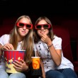 Two young girls watching in cinema — Stock Photo #6692677