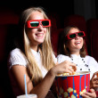 Two young girls watching in cinema — Stock Photo #6692685