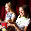 Two young girls watching in cinema — Stock Photo #6692740