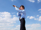 Young business man looks through a telescope — Stock Photo