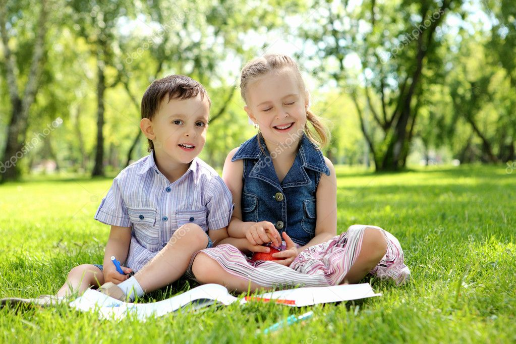 Sister and brother in the park reading a book — Stock Photo #6692522