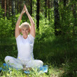 An elderly woman practices yoga — Stock Photo